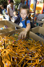 Paul Fraughton | The Salt Lake Tribune Skyler Coulten-Slaten, 7, reaches into a large box of pencils as he fills his bag with school supplies. He was one  of the 150 school-aged children living at The Road Home Shelter who received  back-to-school  items  thanks to the Apple Tree Program, a four-week campaign by the shelter to collect new clothing and school supplies. Apple Trees with paper apples attached, featuring specific children's needs, were set up at various business in the area and participants  bought  items for their chosen  child.  Monday, August 20, 2012