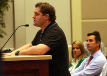 Leah Hogsten  |  The Salt Lake Tribune John Dayton, (left) speaks in favor of Marci and Andrew Kelley's (seated, right) request to amend his Corner Canyon subdivision plan at Draper City Hall council chambers August 21, 2012. Dayton was able to install a bright blue-and-red basketball court after his successful appeal to the City Council to lift a landscaping and development restriction in February that neighbors feel ruins the scenery. The Kelley's undeveloped lot is three lots north of Dayton.