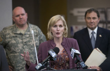 Al Hartmann  |  The Salt Lake Tribune Kristen Cox, executive director for Utah Workforce Services, speaks at a 2011 press conference flanked by Col. Scott Olson of the Utah National Guard and Utah Gov. Gary Herbert. The governor  on Tuesday, Aug. 21, 2012, named her the new head of the Governor's Office of Management and Budget.