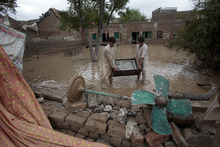 People salvage their belongings following heavy rains in Nowshera, near Peshawar, Pakistan on Wednesday, Aug. 22, 2012. Local meteorologists fear heavy rains fall may cause flooding in some areas of northwest Pakistan. (AP Photo/Mohammad Sajjad)