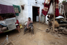 A Pakistani girl sits in her house flooded by heavy rains in Nowshera, near Peshawar, Pakistan on Wednesday, Aug. 22, 2012. Local meteorologists fear heavy rains fall may cause flooding in some areas of northwest Pakistan. (AP Photo/Mohammad Sajjad)