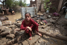 A Pakistani girl sits on fallen part of her house due to heavy raining in Nowshera, near Peshawar, Pakistan on Wednesday, Aug. 22, 2012. Local meteorologists fear heavy rains fall may cause flooding in some areas of northwest Pakistan. (AP Photo/Mohammad Sajjad)