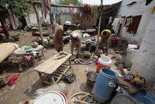 Residents collect their belongings withered by flooding in Nowshera, near Peshawar, Pakistan on Thursday, Aug. 23, 2012. Pakistani officials say heavy monsoon rains that triggered flooding in the country's north have caused dozens of deaths. (AP Photo/Mohammad Sajjad)