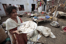 A Pakistani girl carries a flour spoiled by rain water in Nowshera, near Peshawar, Pakistan on Thursday, Aug. 23, 2012. Pakistani officials say heavy monsoon rains that triggered flooding in the country's north have caused dozens of deaths. (AP Photo/Mohammad Sajjad)