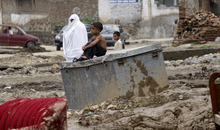 A boy sits on a trunk outside his house collapsed by flooding in Nowshera, near Peshawar, Pakistan on Thursday, Aug. 23, 2012. Pakistani officials say heavy monsoon rains that triggered flooding in the country's north have caused dozens of deaths. (AP Photo/Mohammad Sajjad)