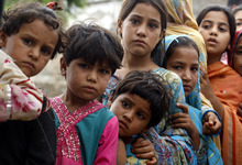 Flood-displaced children stand in a queue to receive medicine from a mobile dispensary in Nowshera, near Peshawar, Pakistan on Thursday, Aug. 23, 2012. Pakistani officials say heavy monsoon rains that triggered flooding in the country's north have caused dozens of deaths. (AP Photo/Mohammad Sajjad)
