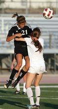 Kim Raff | The Salt Lake Tribune Murray player Samantha Bengtzen heads the ball over Jordan High School player Jacqueline Williams during a girls soccer game at Jordan High School in Sandy, Utah on August 23, 2012.