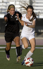 Kim Raff | The Salt Lake Tribune Jordan High School player (right) Jacqueline Williams and Murray player Lizzie Braby battle for the ball during a girls soccer game at Jordan High School in Sandy, Utah on August 23, 2012.