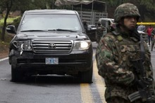 Military stand guard over an armored U.S. Embassy vehicle attacked by unknown assailants on the highway leading to the city of Cuernavaca, near Tres Marias, Mexico, Friday, Aug. 24, 2012. Two U.S. government employees were shot and wounded in an attack on their vehicle south of Mexico City on Friday, a law enforcement official said. (AP Photo/Alexandre Meneghini)