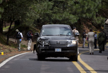 Security personal search for evidence near an armored U.S. Embassy vehicle after it was attacked by unknown assailants on the highway leading to the city of Cuernavaca, near Tres Marias, Mexico, Friday, Aug. 24, 2012. Two U.S.  government employees were shot and wounded in an attack on their vehicle south of Mexico City on Friday, a law enforcement official said. (AP Photo/Alexandre Meneghini)