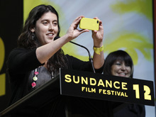 Director Alison Klayman takes a photo after asking the audience to give her the middle finger as she accepts the U.S. Documentary Special Jury Prize: Documentary for the film