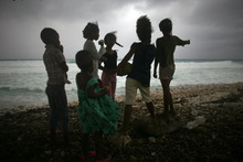 Children look out at the beach as Tropical Storm Isaac approaches in Barahona, Dominican Republic, Friday, Aug. 24, 2012.  Isaac strengthened slightly as it spun toward the Dominican Republic and Haiti, but seemed unlikely to gain enough steam early Friday to strike the island of Hispaniola as a hurricane. The storm's failure to gain the kind of strength in the Caribbean that forecasters initially projected made it more likely that Isaac won't become a hurricane until it enters the Gulf of Mexico, said Eric Blake, a forecaster with U.S. National Hurricane Center in Miami. (AP Photo/Ricardo Arduengo)