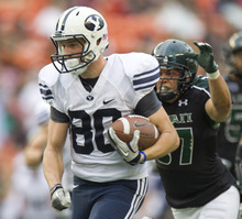 Hawaii safety Kenny Estes, right, makes a touchdown saving tackle on BYU tight end Marcus Mathews (80) in the third quarter of an NCAA college football game, Saturday, Dec. 3, 2011, in Honolulu. (AP Photo/Eugene Tanner)