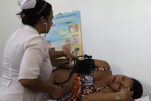 In this Aug 16, 2012 photo, a nurse checks the blood pressure of patient Niurka Rodriguez, who is eight months pregnant at a government run neighborhood clinic in Havana, Cuba. Cuba's system of free medical care, long considered a birthright by its citizens and trumpeted as one of the communist government's great successes, is not immune to cutbacks under Raul Castro's drive for efficiency. The health sector has already endured millions of dollars in budget cuts and tens of thousands of layoffs, and Castro is looking for more ways to save. (AP Photo/Franklin Reyes)