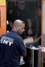 An unidentified woman is treated by emergency medical technicians inside an ambulance following a multiple shooting outside the Empire State Building, Friday, Aug. 24, 2012, in New York. At least four people were shot on Friday morning and the gunman was dead, New York City officials said. A witness said the gunman was firing indiscriminately. Police said as many as 10 people were injured, but it is unclear how many were hit by bullets. A law enforcement official said the shooting was related to a workplace dispute. The official spoke on condition of anonymity because the investigation was ongoing. (AP Photo/Mark Lennihan)