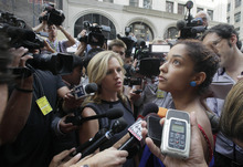 Rebecca Cox talks to media while recounting what she saw immediately following a multiple shooting outside the Empire State Building, Friday, Aug. 24, 2012, in New York. At least four people were shot on Friday morning and the gunman was dead, New York City officials said. A witness said the gunman was firing indiscriminately. Police said as many as 10 people were injured, but it is unclear how many were hit by bullets. A law enforcement official said the shooting was related to a workplace dispute. The official spoke on condition of anonymity because the investigation was ongoing.  (AP Photo/Mark Lennihan)