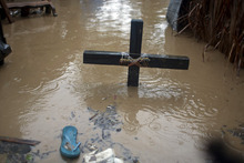 A voodoo cross in honor of the Baron Samedi stands in floodwaters, triggered by Tropical Storm Isaac, at a place of worship in Port-au-Prince, Haiti, Saturday, Aug. 25, 2012. Tropical Storm Isaac swept across Haiti's southern peninsula early Saturday, dousing a capital city prone to flooding and adding to the misery of a poor nation still trying to recover from the 2010 earthquake. (AP Photo/Dieu Nalio Chery)