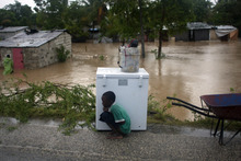 A boy tries to take cover from the cold behind an appliance sitting higher than the floodwaters triggered by Tropical Storm Isaac in Port-au-Prince, Haiti, Saturday Aug. 25, 2012. Tropical Storm Isaac swept across Haiti's southern peninsula early Saturday, dousing a capital city prone to flooding and adding to the misery of a poor nation still trying to recover from the 2010 earthquake. (AP Photo/Dieu Nalio Chery)