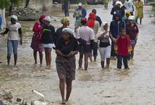 In this photo released by the U.N. mission in Haiti, MINUSTAH, residents leave their flooded homes in a low lying area affected by Tropical Storm Isaac in Port-au-Prince, Haiti, Saturday, Aug. 25, 2012. Tropical Storm Isaac swept across Haiti's southern peninsula early Saturday, dousing a capital city prone to flooding and adding to the misery of a poor nation still trying to recover from the 2010 earthquake. (AP Photo/MINUSTAH, Logan Abassi)