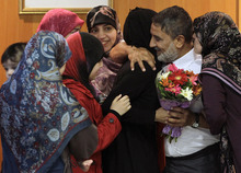 Hussein Ali Omar, 60, one of 11 Lebanese Shiite pilgrims that Syrian rebels have been holding for three months in Syria, is welcomed by his daughters on arrival at Rafik Hariri international airport, in Beirut, Lebanon, Saturday Aug. 25, 2012. Syrian rebels freed Omar on Saturday in a move aimed at easing cross-border tensions after a wave of abductions of Syrian citizens in Lebanon. The Shiite pilgrims were abducted May 22 after crossing into Syria from Turkey on their way to Lebanon. (AP Photo/Hussein Malla)