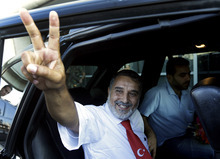 Hussein Ali Omar, 60, one of 11 Lebanese Shiite pilgrims that Syrian rebels have been holding for three months in Syria, flashes the victory sign on arrival at Rafik Hariri international airport, in Beirut, Lebanon, Saturday Aug. 25, 2012. Syrian rebels freed Omar on Saturday in a move aimed at easing cross-border tensions after a wave of abductions of Syrian citizens in Lebanon. The Shiite pilgrims were abducted May 22 after crossing into Syria from Turkey on their way to Lebanon. (AP Photo/Hussein Malla)