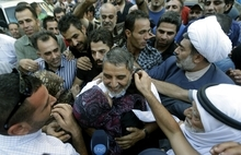 Hussein Ali Omar, 60, one of 11 Lebanese Shiite pilgrims that Syrian rebels have been holding for three months in Syria, is escorted by his relatives and hugged by his wife upon arrival at his home, in Beirut, Lebanon, Saturday Aug. 25, 2012. Syrian rebels freed Omar on Saturday in a move aimed at easing cross-border tensions after a wave of abductions of Syrian citizens in Lebanon. The Shiite pilgrims were abducted May 22 after crossing into Syria from Turkey on their way to Lebanon. (AP Photo/Hussein Malla)