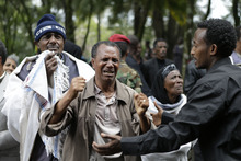 People react as they arrive in front of the coffin of Prime Minister Meles Zenawi, at the prime minister's official residence the national palace, in Addis Ababa, Ethiopia Saturday, Aug. 25, 2012. In an emotional outpouring of national grief, Ethiopians continued to line up by the thousands Saturday to pay their respects to Zenawi, who died Monday, Aug. 20 of an unknown illness. Zenawi is scheduled to be buried on Sept. 2. (AP Photo/Rebecca Blackwell)