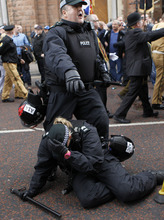 A police officer is injured on the ground after trying to stop fighting between loyalist and Nationalist groups outside outside St Patrick's Roman Catholic Church in Belfast, Northern Ireland, Saturday, Aug. 25, 2012. Trouble broke out after loyalist bands marched past the church while playing music that was banned by the parades commission.  (AP Photo/Peter Morrison