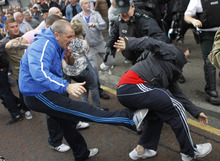 A police officer, center background, tries to stop fighting between loyalist and Nationalist groups outside outside St Patrick's Roman Catholic Church in Belfast, Northern Ireland, Saturday, Aug. 25, 2012. Trouble broke out after loyalist bands marched past the church while playing music that was banned by the parades commission.  (AP Photo/Peter Morrison
