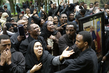 People react in front of the coffin of Prime Minister Meles Zenawi, at the prime minister's official residence, the national palace, in Addis Ababa, Ethiopia Saturday, Aug. 25, 2012. In an emotional outpouring of national grief, Ethiopians continued to line up by the thousands Saturday to pay their respects to Zenawi, who died Monday, Aug. 20 of an unknown illness. Zenawi is scheduled to be buried on Sept. 2. (AP Photo/Rebecca Blackwell)