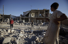 Syrian boys play next to a house destroyed in a Syrian government bombing last week that killed more than 40 people, in Azaz, on the outskirts of Aleppo, Syria, Friday, Aug. 24, 2012. (AP Photo/Muhammed Muheisen)