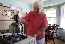 In this photo taken July 26, 2012, Marge Youngs adjusts the flame on her stove at her home in Toledo, Ohio. When given a choice on how to fix Social Security's serious long-term financial problems, 53 percent of adults said they would rather raise taxes than cut benefits for future generations, according to an Associated Press-GfK poll.
