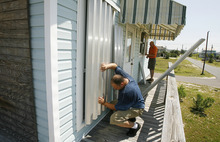 Larry Hoffmeister, left, and Charles Carter, both of Semmes, Ala., cover windows of Carter's vacation/rental home as residents and property owners prepare for Tropical Storm Isaac on Sunday, Aug. 26, 2012, in Dauphin Island, Ala. (AP Photo/Press-Register, Mike Kittrell) MAGS OUT