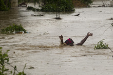 In this photo released by the U.N. mission in Haiti, MINUSTAH, a woman swims through flood waters in a low lying area affected by Tropical Storm Isaac in Port-au-Prince, Haiti, Saturday, Aug. 25, 2012. Tropical Storm Isaac swept across Haiti's southern peninsula early Saturday, dousing a capital city prone to flooding and adding to the misery of a poor nation still trying to recover from the 2010 earthquake. (AP Photo/MINUSTAH, Logan Abassi)