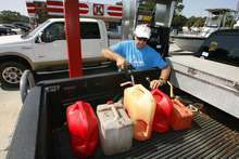 Richard McKean buys gas for a generator as residents and property owners prepare for Tropical Storm Isaac on Sunday, Aug. 26, 2012, in Dauphin Island, Ala. (AP Photo/Press-Register, Mike Kittrell) MAGS OUT