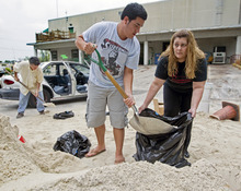 Connie Rivero and her son Anthony Amador fill plastic bags with sand at the Hollywood Public Works Department as they prepare for possible floods from Tropical Storm Isaac on Saturday, Aug. 25, 2012, in Hollywood, Fla. Isaac was expected to pass over the Florida Keys as a hurricane late Sunday or early Monday. (AP Photo/The Miami Herald, Al Diaz)  MAGS OUT