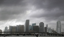 Heavy storm clouds hover over the skyline of downtown Miami as Tropical Storm Isaac's weather bands reach the Miami area aon Sunday, Aug. 26, 2012. Isaac gained fresh muscle Sunday as it bore down on the Florida Keys, with forecasters warning it could grow into a dangerous Category 2 hurricane as it nears the northern Gulf Coast. (AP Photo/The Miami Herald, Carl Juste)