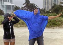 Victoria Balladares and boyfriend Jose Requejo experience the rain at Miami Beach as Tropical Storm Isaac hits the area on Sunday, Aug., 26, 2012, in Miami. Isaac gained fresh muscle Sunday as it bore down on the Florida Keys, with forecasters warning it could grow into a dangerous Category 2 hurricane as it nears the northern Gulf Coast. (AP Photo/The Miami Herald, Carl Juste)
