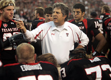FILE - In this Oct. 24, 2009, file photo, Texas Tech coach Mike Leach talks with his team during an NCAA college football game against Texas A&M in Lubbock, Texas. Leach has been suspended while the school investigates complaints from a player and his family about treatment after an injury. (AP Photo/Mike Fuentes, File)