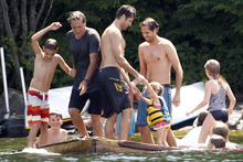 FILE - In this July 6, 2012, file photo Republican presidential candidate Mitt Romney, top second from left, plays with family and friends on a floating raft on Lake Winnipesaukee in Wolfeboro, N.H.  The Romneys envision a White House enlivened by