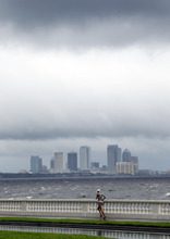 A woman jogs along Bayshore Boulevanrd in between squalls blowing across the bay in Tampa, Fla., Monday, Aug. 27, 2012. The Republican National Convention has delayed it's start because of the approaching tropical storm Isaac which is churning it's way across the Gulf of Mexico. (AP Photo/Chris O'Meara)