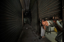 A shopkeeper looks out from inside a closed shop during a 12 hours general strike called by radical Hindu group Bajrang Dal in Gauhati, Assam state, India, Monday, Aug. 27, 2012. The strike was to protest the recent ethnic violence in the state which killed at least 80 people and displaced 400,000. Bajrang Dal also demanded sealing of the India Bangladesh border to stop the ongoing violence. (AP Photo/Anupam Nath)