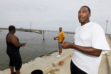 Rayfus McLauren of Gulfport, is not sure when he and his family will evacuate their homes, from the storm surges from Tropical Storm Isaac, but for now he and his brothers-in-law, Vincent Williams, left, and Billie Braziel, back, are enjoying a last day of fishing in Long Beach, Miss., Monday, Aug. 27, 2012. Officials at the almost 300 slip harbor made vessel evacuation mandatory Monday. (AP Photo/Rogelio V. Solis)