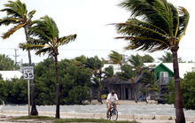 A cyclist rides his bike in Key West, Fla., Sunday, Aug. 26, 2012. Tropical Storm Isaac gained fresh muscle Sunday as it bore down on the Florida Keys, with forecasters warning it could grow into a dangerous Category 2 hurricane as it nears the northern Gulf Coast. (AP Photo/Alan Diaz)