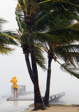 A person braves the rain at Clarence Higgs Beach in Key West, Fla., as Tropical Storm Isaac hits the area on Sunday, Aug., 26, 2012. Isaac gained fresh muscle Sunday as it bore down on the Florida Keys, with forecasters warning it could grow into a dangerous Category 2 hurricane as it nears the northern Gulf Coast. (AP Photo/The Miami Herald, Walter Michot)
