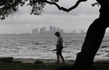 John Hassell walks his dog in between squalls blowing across Tampa Bay at Ballast Park in Tampa, Fla., Monday, Aug. 27, 2012. The Republican National Convention has delayed it's start because of the approaching tropical storm Isaac which is churning it's way across the Gulf of Mexico. (AP Photo/Dave Martin)