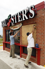 Daniel Shedd, left, and George Lopez board up a local Bruster's in Gulf Shores, Ala. on Monday, Aug. 27, 2012. The National Hurricane Center predicted Isaac would grow to a Category 1 hurricane over the warm Gulf and possibly hit late Tuesday somewhere along a roughly 300-mile (500-kilometer) stretch from the bayous southwest of New Orleans to the Florida Panhandle. The size of the warning area and the storm's wide bands of rain and wind prompted emergency declarations in four states, and hurricane-tested residents were boarding up homes, stocking up on food and water or getting ready to evacuate.  (AP Photo/Butch Dill)