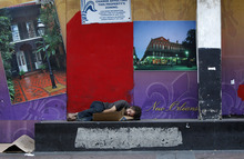 A man sleeps outside a boarded-up building on Canal Street in New Orleans Tuesday, Aug. 28, 2012, prior to the approach of Isaac, which is expected to reach the swampy coast of southeast Louisiana by early Wednesday. The U.S. National Hurricane Center said the storm, with 75 mph (120 kph) winds, had gained strength as it moved over the warm, open waters of the Gulf of Mexico. (AP Photo/Gerald Herbert)