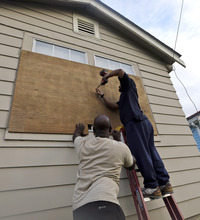 Stacey Davis, left, and his board up windows on their home before Tropical Storm Isaac hits Tuesday, Aug. 28, 2012, in New Orleans. Tropical Storm Isaac is churning it's way across the Gulf of Mexico towards New Orleans. (AP Photo/David J. Phillip)