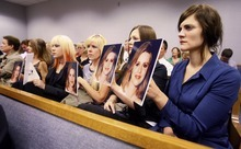 Family members of Martin Joseph MacNeill hold photos of Michele MacNeill up facing mr. Macneill as he makes his initial appearance Monday, Aug. 27, 2012 before Judge Samuel D. McVey in Provo.